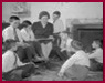 thumbnail for Tips and Tricks showing Female teacher on couch reading to young boys gathered around her on floor.